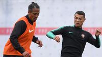 Bek Portugal, Bruno Alves berebut bola dengan Cristiano Ronaldo saat latihan di Kratovo, Moskow (10/6). Bek 36 tahun ini menjalani laga ke-100-nya di Piala Dunia 2018 ini.  Saat ini Alves bermain di Rangers FC. (AFP Photo/Francisco Leong)