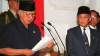 Soeharto didampingi wakilnya, BJ Habibie, membacakan pidato pengunduran dirinya sebagai Presiden RI pada 21 Mei 1998. Soeharto yang telah telah menjadi presiden Indonesia selama 32 tahun mundur setelah runtuhnya dukungan untuk dirinya. (AGUS LOLONG/AFP)