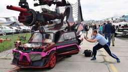 Seorang pengunjung mengambil gambar dari sebuah mobil yang dihias selama hari pembukaan festival mobil retro OldCarLand di Kiev (27/4). Pameran kendaraan jadul ini digelar dari 27 April hingga Mei, 1, 2018. (AFP Photo/Sergei Supinsky)
