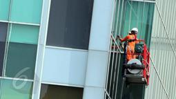 Pekerja sedang membersihkan kaca gedung bertingkat di kawasan Kuningan, Jakarta, Selasa (3/6). Menaker Hanif Dhakiri mengatakan angka kecelakaan kerja secara nasional masih sangat tinggi yaitu 103.000 per tahunnya. (Liputan6.com/Helmi Afandi)
