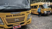 Salah satu sopir turun dari bus sekolah usai melakukan dekontaminasi di Pool Unit Pelayanan Angkutan Sekolah (UPAS) DKI Jakarta, Kramat Jati, Selasa (5/1/2021). Usai bertugas mengantarkan pasien Covid-19, para sopir bus sekolah tersebut rutin melakukan dekontaminasi. (merdeka.com/Iqbal Nugroho)