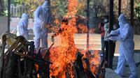 Anggota keluarga dan kerabat yang mengenakan alat pelindung diri menyiapkan tumpukan kayu pemakaman untuk mengkremasi korban COVID-19 di krematorium di New Delhi, India, Senin (24/5/2021). Kematian akibat COVID-19 di India telah menembus 300 ribu orang. (Sajjad HUSSAIN/AFP)