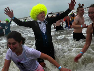 Warga Belgia berbondong-bondong menyerbu perairan Laut Utara untuk merayakan akhir pekan perrtama 2019 di Ostend, Sabtu (5/1). Tak sekadar bermain air, sebagian warga juga beraksi dengan kostum berwarna-warni. (AP/Francisco Seco)