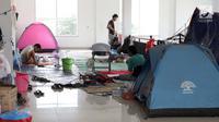 Sejumlah pencari suaka mendirikan tenda di dalam gedung bekas Markas Kodim, Kalideres, Jakarta, Selasa (3/9/2019). Pemprov DKI Jakarta memberikan batas waktu hingga 31 Agustus 2019,  namun masih banyak pencari suaka memilih bertahan di gedung itu. (Liputan6.com/Helmi Fithriansyah)