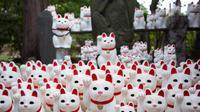 Patung-patung kucing yang disebut maneki-neko menghiasi kuil Gotokuji di Tokyo, Jepang, 6 Agustus 2018. Kuil Gotokuji di Tokyo telah lama menarik pengunjung dengan ribuan patung kucing putihnya, yang dianggap membawa keberuntungan. (AFP/Martin BUREAU)