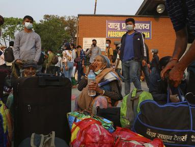 Seorang perempuan meminum obatnya saat menunggu bus untuk kembali ke desa sehari sebelum lockdown di Kathmandu, Rabu (28/4/2021). Puluhan ribu orang meninggalkan ibu kota Nepal sehari menjelang lockdown selama 15 hari yang diberlakukan karena melonjaknya kasus COVID-19. (AP Photo/Niranjan Shrestha)