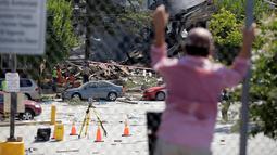Warga melihat petugas pemadam yang tengah bekerja di reruntuhan apartemen di Sivler Spring, Maryland, Washington DC, Kamis (11/8). Ledakan terjadi akibat adanya kebocoran antara pipa gas yang mengaliri apartemen itu dengan kompor. (REUTERS/Joshua Roberts)