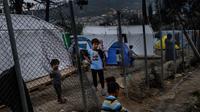 Anak-anak imigran bermain di sebelah pagar di luar kamp pengungsi di pulau Samos, Yunani (13/11/2019). Kamp Samos, awalnya dibangun untuk menampung 650 orang, telah lama melampaui batas-batasnya. (AFP Photo/Angelos Tzortzinis)