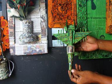 Perajin menunjukkan miniatur pesawat di bengkel Workshop kawasan Kemandoran 8 Jakarta Selatan, Senin (10/2/2020). Berbagai kerajinan berwujud keranjang, wadah, lampu belajar, miniatur pesawat dan motor berbahan dasar koran bekas dijual Rp. 50.000 ribu hingga Rp 150 ribu. (merdeka.com/Arie Basuki)