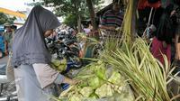 Seorang wanita memilih kulit ketupat di Pasar Minggu, Jakarta Selatan, Senin (4/7). H-2 Hari Raya Idul Fitri, pedagang kulit ketupat mulai kebanjiran pembeli. (Liputan6.com/Yoppy Renato)