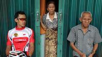 Pebalap sepeda Timnas Indonesia, Aiman Cahyadi beristirahat di teras toko warga saat berhenti di Barung-Barung Belantai dalam Etape 1 Tour de Singkarak 2015, Sabtu (3/10/2015). (Bola.com/Arief Bagus)
