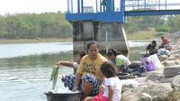 Sembari mengasuh anak, ibu-ibu nekat mencuci di bibir Waduk Sangge. Foto: (Felek/Liputan6.com)