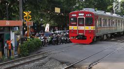 Kereta api melintas di kawasan Lenteng Agung, Jakarta, Kamis (14/3). Untuk mengurai kemacetan, Pemprov DKI Jakarta akan membangun jalan layang (fly over) berbentuk tapal kuda di perlintasan tersebut. (Liputan6.com/Immanuel Antonius)