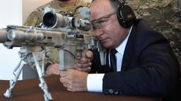 Presiden Rusia, Vladimir Putin menguji coba senapan sniper Chukavin (SVC-380) saat mengunjungi pameran Kalashnikov Concern di Patriot Park, luar Moskow, Rabu (19/9). Kalashnikov merupakan produsen senjata terkenal di dunia. (Alexey NIKOLSKY/SPUTNIK/AFP)