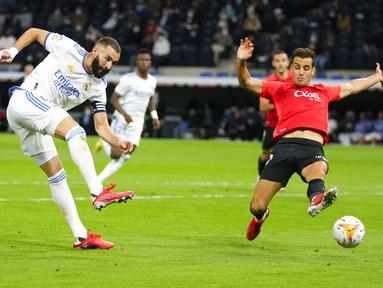 Penyerang Real Madrid Karim Benzema (kiri) mencetak gol kelima untuk timnya ke gawang Mallorca pada jornada keenam La Liga Spanyol di Santiago Bernabeu, Kamis (23/9/2021) dini hari WIB. Real Madrid berpesta gol usai melibas Real Mallorca 6-1. (AP Photo/Manu Fernandez)