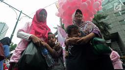 """Anak-anak memeluk ibunya saat acara """"Peluk Ibu Satu Indonesia""""  selama Car Free Day di Bundaran HI, Jakarta, Minggu (23/12). Acara itu dalam rangka memperingati hari ibu dan mengajak masyarakat untuk selalu menghormati ibu. (Merdeka.com/Iqbal S. Nugroho)"""