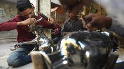 Perajin membuat kerajinan gajah dari kuningan di sebuah bengkel di Karachi, Pakistan (19/11/2019). Perajin kuningan di Karachi biasa membuat patung, hewan, vas lilin dan lentera dari segala bentuk dan ukuran. (AFP Photo/Asif Hassan)