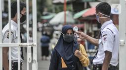 Petugas keamanan memeriksa suhu tubuh orangtua dari anak penerima KJP sebelum memasuki area pengambilan kartu di kawasan Matraman, Jakarta, Selasa (24/11/2020). (merdeka.com/Iqbal S. Nugroho)