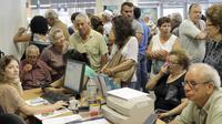 Sejumlah pensiunan menunggu di loket bank untuk mendapatkan uang pensiunan mereka di bank nasional di Iraklio, Yunani, (9/7/2015). Banyak bank di Yunani tutup dan penarikan uang tunai dari ATM dibatasi hanya 67 dolar sehari. (REUTERS/Stefanos Rapanis)