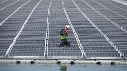 Petugas memeriksa panel surya fotovoltaik mengapung di kompleks pembangkit listrik O'Mega1 di Piolenc, Prancis selatan (30/7/2019). Pembangkit listrik tenaga surya (PLTS) mengapung pertama di Eropa ini akan beroperasi pada September 2019. (AFP Photo/Gerard Julien)