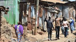 Henry Ohanga alias Octopizzo (tengah) berjalan dengan seorang teman saat berkunjung ke Kibera di Nairobi, Kenya (16/1). Seperti kebanyakan anak muda di daerah kumuh ini, Octopizzo berpikir dia tidak akan pernah menjadi apa-apa. (AFP Photo/Tony Karumba)