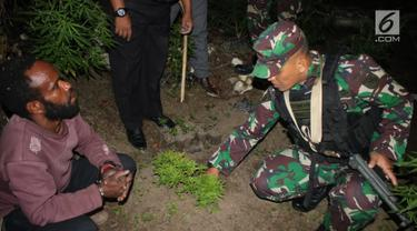 Danyonif Raider 756 Mayor Inf Arif Budi Situmeang menunjukkan pelaku pengedar ganja  Apianus Logo dan barang bukti di jalan lintas Wamena-Karubaga-Puncak Jaya di Kampung Kurulu, Papua, Jumat (3/8). (Liputan6.com/HO/Dispenad)