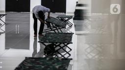 Petugas menyiapkan tempat isolasi di Aula Masjid KH Hasyim Asyari atau Masjid Raya Jakarta, Daan Mogot, Jumat (25/6/2021). Pemprov DKI menetapkan sejumlah lokasi menjadi tempat isolasi mandiri warga yang positif COVID-19, salah satunya adalah Masjid KH Hasyim Asyari. (Liputan6.com/Johan Tallo)