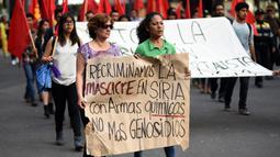 Demonstran membawa tulisan saat menggelar aksi di depan Kedubes AS di Mexico City, Minggu (9/4). Mereka mengecam serangan bom kimia yang telah menewaskan warga Suriah dan menolak intervensi AS. (AFP PHOTO / Pedro Pardo)