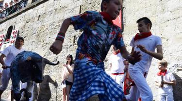 Anak-anak berlarian saat mengikuti Encierro Txiki selama Festival San Fermin di Pamplona, Spanyol (13/7). Encierro Txiki  atau Small Bull Run ini adalah bagian dari Festival San Fermin yang khusus untuk anak-anak. (AFP Photo/Ander Gillenea)