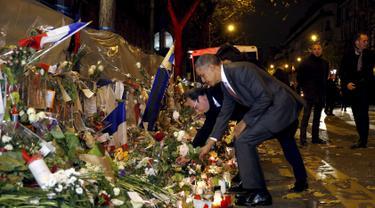 Presiden AS, Barack Obama dan Presiden Prancis, Francois Hollande meletakkan bunga di salah satu lokasi serangan berdarah Paris di gedung konser Bataclan, Prancis, Minggu (30/11). (REUTERS/Philippe Wojazer)