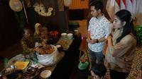 Putra sulung Presiden Jokowi, Gibran Rakabuming Raka bersama istri dan anaknya Jan Ethes sedang membeli camilan olahan jahe yang kian langka di Traditional Dessert Festival di The Sunan Hotel Solo, Selasa malam (29/10).(Liputan6.com/Fajar Abrori)