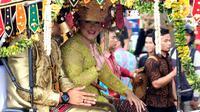Pasangan Kahiyang Ayu Siregar dan Bobby Nasution menyapa warga saat kirab resepsi pernikahan Kahiyang Ayu-Bobby Nasution di Kota Medan, Sumatera Utara, Minggu (26/11). (Liputan6.com/Johan Tallo)