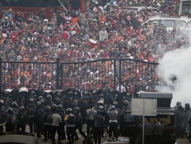 Petugas Kepolisian berusaha menghalau suporter Persija Jakarta yang memaksa masuk komplek SUGBK untuk menyaksikan laga melawan Mitra Kukar pada laga Liga 1, Jakarta, Minggu (09/12). Persija menang 2-1 atas Mitra Kukar. (Bola.com/M Iqbal Ichsan)