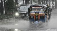 Bajaj saat menerobos hujan di Jalan Pramuka, Jakarta, Kamis (18/2/2021). Badan Meteorologi Klimatologi dan Geofisika (BMKG) mengimbau pengguna jalan agar berhati-hati saat berkendara karena hujan disertai angin kencang diprediksi terus berlanjut hingga akhir Februari. (merdeka.com/Iqbal S Nugroho)