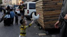Seorang anak Yahudi ultra-Ortodoks bermain dengan balon berbentuk ayam selama ritual Kaparot di Yerusalem, Rabu (23/9/2020). Sebagian percaya, ritual Kaparot akan membebaskan mereka dari dosa-dosa yang ditransfer ke ayang yang dipotong.  (AP Photo/Maya Alleruzzo)