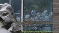 Anggota tim WHO mengenakan APD selama kunjungan lapangan ke Pusat Pengendalian dan Pencegahan Penyakit Hewan Hubei di Wuhan di provinsi Hubei, China tengah, Selasa (2/2/2021). Kunjungan tim WHO ke berbagai tempat itu dijadwalkan akan berlangsung selama dua pekan.  (AP Photo/ Ng Han Guan)