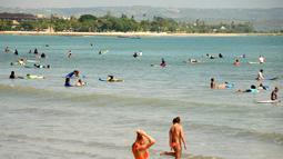 Turis berselancar di pantai Kuta dekat Denpasar di pulau resor Indonesia di Bali (3/5). Daerah ini merupakan sebuah tujuan wisata turis mancanegara dan telah menjadi objek wisata andalan Pulau Bali sejak awal tahun 1970-an. (AFP Photo/Sonny Tumbelaka)