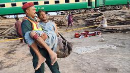 Petugas mengevakuasi seorang penumpang yang terluka dalam kecelakaan dua kereta di distrik Rahim Yar Khan, Pakistan, Kamis (11/7/2019). Kecelakaan terjadi ketika kereta penumpang yang sedang melaju dari arah timur kota Lahore menabrak kereta barang yang berhenti di persimpangan. (Photo by STR / AFP)