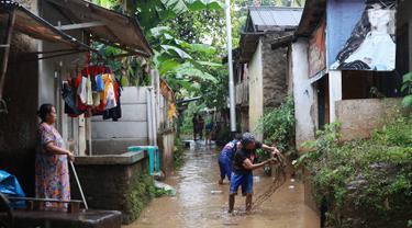 Warga membersihkan lumpur dari banjir yang menggenangi Gang Arus Dalam di Cawang, Jakarta Timur, Rabu (24/4). Banjir kiriman dari Bogor yang menggenangi kawasan tersebut menyisakan lumpur dan sampah sehingga menganggu aktivitas warga. (Liputan6.com/Immanuel Antonius)