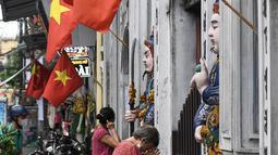 Umat Buddha berdoa di luar pagoda Cau Dong saat perayaan Hari Waisak di Hanoi, Vietnam pada Rabu (26/5/2021). Tempat ibadah di kawasan tersebut ditutup untuk mencegah penyebaran virus corona Covid-19. (Nhac NGUYEN / AFP)