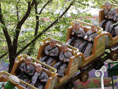 Para biksu cilik menaiki roller coaster saat mengunjungi taman hiburan Everland di Yongin, Korea Selatan, Kamis (2/5). Kunjungan ini merupakan bagian dari program pelatihan mereka saat belajar agama Buddha. (AP Photo/Lee Jin-man)