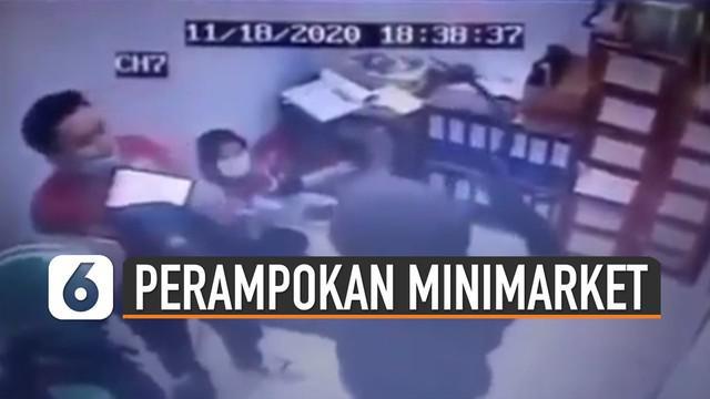 Terlihat dua orang perampok sedang mengancam dua karyawan minimarket.