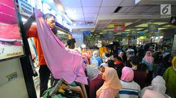 Pedagang melayani pembeli di pasar Tanah Abang, Jakarta, Minggu (26/5/2019). Jelang lebaran masyarakat mulai memadati pusat perbelanjaan untuk membeli kebutuhan saat Hari Raya Idul Fitri. (Liputan6.com/Angga Yuniar)