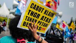 Seorang pengunjuk rasa menunjukkan poster saat menggelar aksi di depan Istana Negara, Jakarta, Senin (25/9). Aksi tersebut sebagai peringatan Hari Tani Nasional (HTN) 2017. (Liputan6.com/Faizal Fanani)