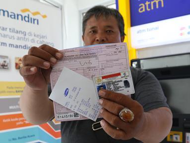 Warga menunjukkan bukti pembayaran tilang online melalui atm Bank Mandiri di Jakarta, Kamis (3/1). Bank Mandiri berkerjasama dengan Kejari Jakpus dalam penerimaan pembayaran tilang non tunai atau secara online. (Liputan6.com/Angga Yuniar)