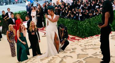 Rapper 2 Chainz berlutut saat sang kekasih, Kesha Ward memperlihatkan cincin pada Met Gala 2018 di Metropolitan Museum of Art, New York, Senin (7/5). Dalam acara Met Gala, Chainz melamar sang kekasih yang telah memberikannya dua putri. (AP/John Carucci)