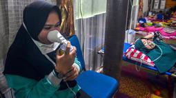Warga yang terpapar kabut asap karhutla menghirup oksigen ketika berada di Rumah Singgah Korban Asap di Pekanbaru, Riau, Jumat (20/9/2019). Data Kemenkes sebanyak 15.346 warga di Provinsi Riau menderita ISPA akibat kabut asap karhutla dalam kurun waktu September 2019. (Wahyudi/AFP)