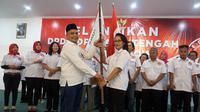 Ketua Umum DPP Sedulur Jokowi, Paiman Rahardjo menyerahkan panji kepada Ketua DPD Sedulur Jokowi Jawa Tengah, Baningsih Tedjokartono saat pelantikan di RM Tamansari, Karanganyar, Kamis (27/12).(Liputan6.com/Fajar Abrori0