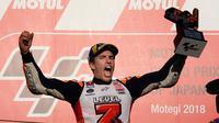 Pembalap Repsol Honda, Marc Marquez berselebrasi di atas podium setelah memenangi balapan MotoGP Jepang 2018 di Twin Ring Motegi, Minggu (21/10). Kemenangan Marquez di Jepang sekaligus membuatnya menjadi juara dunia MotoGP 2018. (AP/Shizuo Kambayashi)