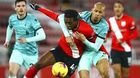 Gelandang Liverpool, Fabinho, berebut bola dengan pemaIn Southampton, San Nlundulu, pada laga Liga Inggris di Stadion St Mary's, Selasa (05/01/2021). Liverpool takluk 1-0 dari Southampton. (AP Photo/Michael Steele,Pool)